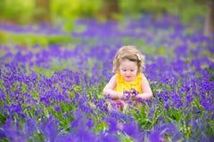 Den gulliga litet barnflickan i blåklocka blommar i vår Royaltyfri Foto