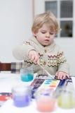 Den gulliga litet barnpojken som har roligt inomhus och att måla med olikt, smärtar Royaltyfria Foton