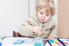 Den gulliga litet barnpojken som har roligt inomhus och att måla med olikt, smärtar Royaltyfria Bilder