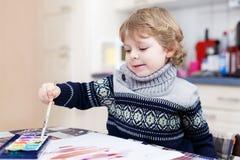 Den gulliga litet barnpojken som har roligt inomhus och att måla med olikt, smärtar Arkivfoton