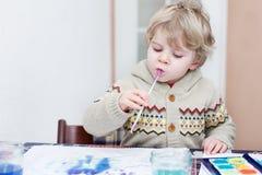 Den gulliga litet barnpojken som har roligt inomhus och att måla med olikt, smärtar Royaltyfri Bild