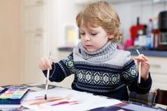 Den gulliga litet barnpojken som har roligt inomhus och att måla med olikt, smärtar Royaltyfri Foto