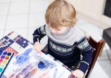 Den gulliga litet barnpojken som har roligt inomhus och att måla med olikt, smärtar Fotografering för Bildbyråer