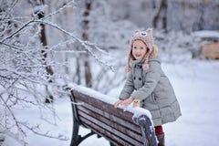 Den gulliga lyckliga barnflickan på gå i den snöig vintern parkerar Arkivbilder