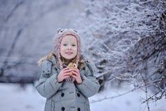Den gulliga lyckliga barnflickan på gå i den snöig vintern parkerar Royaltyfri Foto