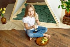 Den gulliga lyckliga lilla flickan med blont hår i en vit skjorta och jeans sitter nära ett tält med en glasflaska av arkivfoton