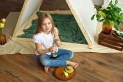Den gulliga lyckliga lilla flickan med blont hår i en vit skjorta och jeans sitter nära ett tält med en glasflaska av arkivfoto