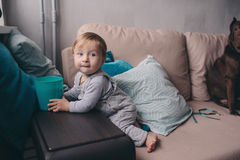 Den gulliga lyckliga 11 månaden behandla som ett barn pojken som hemma spelar, livsstiltillfångatagandet i hemtrevlig inre Royaltyfria Foton