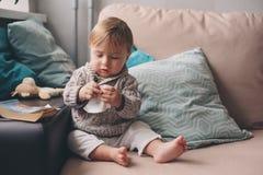 Den gulliga lyckliga 11 månaden behandla som ett barn pojken som hemma spelar, livsstiltillfångatagandet i hemtrevlig inre Royaltyfri Fotografi