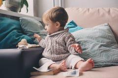 Den gulliga lyckliga 11 månaden behandla som ett barn pojken som hemma spelar, livsstiltillfångatagandet i hemtrevlig inre Arkivbilder