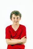 Den gulliga lyckliga pojken i röd skjorta och leasuren poserar arkivfoton