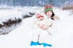Den gulliga lyckliga skratta brodern och behandla som ett barn systern i snö royaltyfri fotografi
