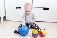 Den gulliga 6 månaden behandla som ett barn flickalekbollar Fotografering för Bildbyråer