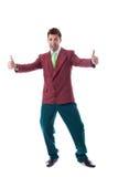 Den gulliga mannen i färgrik dräktvisning tummar upp Royaltyfri Bild