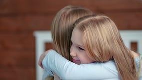 Den gulliga närbilden för sidosikten behandla som ett barn flickan som tycker om att krama med modern hemma lager videofilmer