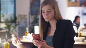 Den gulliga nätta blondinen i det svarta omslaget sitter i caféen Hon smsar med en vän, medan äta hennes lunch lager videofilmer
