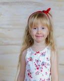 Den gulliga nätta lilla blonda flickan med ett lyckligt grinar royaltyfri bild