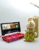 Den gulliga nallebjörnen i ett vitt rum skiner på en kosmetisk spegel Arkivfoton