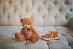 Den gulliga nallebjörnen och skor för barn` s av den samma färgen ligger bredvid på soffan arkivbilder