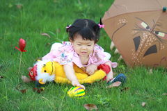 Den gulliga oskyldiget behandla som ett barn den flotta leksaken för flickalek och klumpa ihop sig på gräsmattan Royaltyfri Bild
