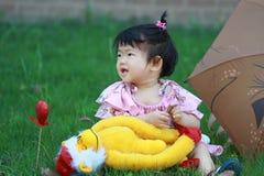 Den gulliga oskyldiget behandla som ett barn den flotta leksaken för flickalek på gräsmattan Arkivfoton