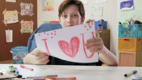 Den gulliga pojkeattraktionbilden som säger ÄLSKAR JAG, U och shower det som ser kameran arkivfilmer