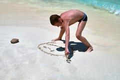 Den gulliga pojken drar en smileyframsida på sanden i form av en sol Tropisk strand, kust som ler solsymbol nära övre för bakgrun arkivbild