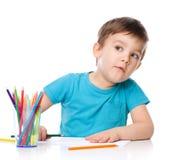 Den gulliga pojken drar genom att använda färgblyertspennor royaltyfri bild
