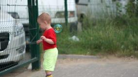 Den gulliga pojken fångar såpbubblor på bakgrunden av suddiga bilar i ultrarapid stock video