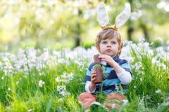 Den gulliga pojken för den lilla ungen med öron för påskkaninen som firar det lyckliga barnet för den traditionella festmåltiden  Royaltyfri Foto