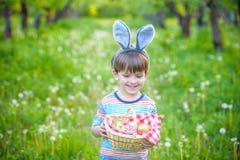 Den gulliga pojken för den lilla ungen med kaninöron som har gyckel med traditionella påskägg, jagar arkivbilder