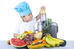 Den gulliga pojken gör fruktfruktsaft Arkivbilder
