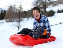 Den gulliga pojken har gyckel med att guppa på det snöig berget Arkivfoton