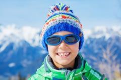 Den gulliga pojken i en vinter skidar semesterorten royaltyfri fotografi