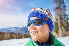 Den gulliga pojken i en vinter skidar semesterorten royaltyfri foto