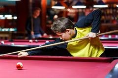 Den gulliga pojken i gul t-skjorta spelar billiard eller pölen i klubba Den unga ungen lär att spela snooker Pojke med billiardst royaltyfria foton