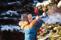 Den gulliga pojken i varm clouth och hatten som fångar jul, klumpa ihop sig i vinter parkerar Ungar spelar utomhus- i snöig skog Arkivbild