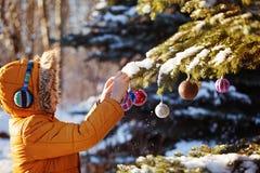 Den gulliga pojken i varm torkduk och hatten som fångar jul, klumpa ihop sig i vinter parkerar Ungelek som är utomhus- i snöig sk Royaltyfri Foto