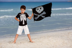 Den gulliga pojken klädde som piratkopierar på den tropiska stranden Fotografering för Bildbyråer