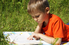 Den gulliga pojken läser boken Royaltyfri Fotografi