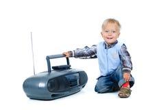den gulliga pojken lyssnar little musik till Fotografering för Bildbyråer