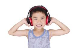 Den gulliga pojken lyssnar till musik Arkivfoto