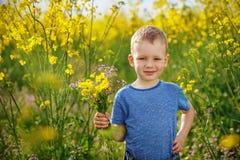 Den gulliga pojken med en bukett av blommor är i de gula blomningrommarna Arkivbilder