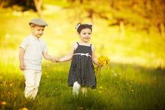 Den gulliga pojken och flickan på sommar sätter in Fotografering för Bildbyråer