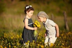 Den gulliga pojken och flickan på sommar sätter in Royaltyfri Bild