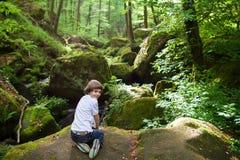 Den gulliga pojken på vaggar nära en scenisk vattenfall Royaltyfria Bilder