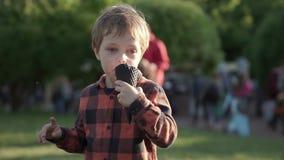 Den gulliga pojken som äter rosa glass i kotte på offentligt, parkerar stock video