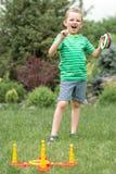 Den gulliga pojken som spelar en lek som kastar cirklar i sommar, parkerar utomhus Gl?djen av segern arkivfoto