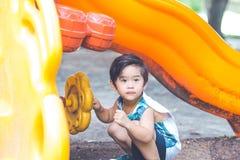 den gulliga pojken spelar i lekplatsen Arkivbilder