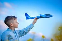 Den gulliga pojken spelar med ett leksakflygplan i den blåa himlen och drömmarna av loppet Hand med den bl?a leksakniv?n arkivfoto